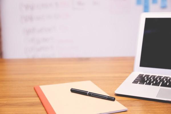 escritorio con portátil y bloc de notas