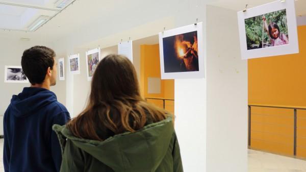 Dos estudiantes contemplan las fotos de la exposición en la Biblioteca UPO